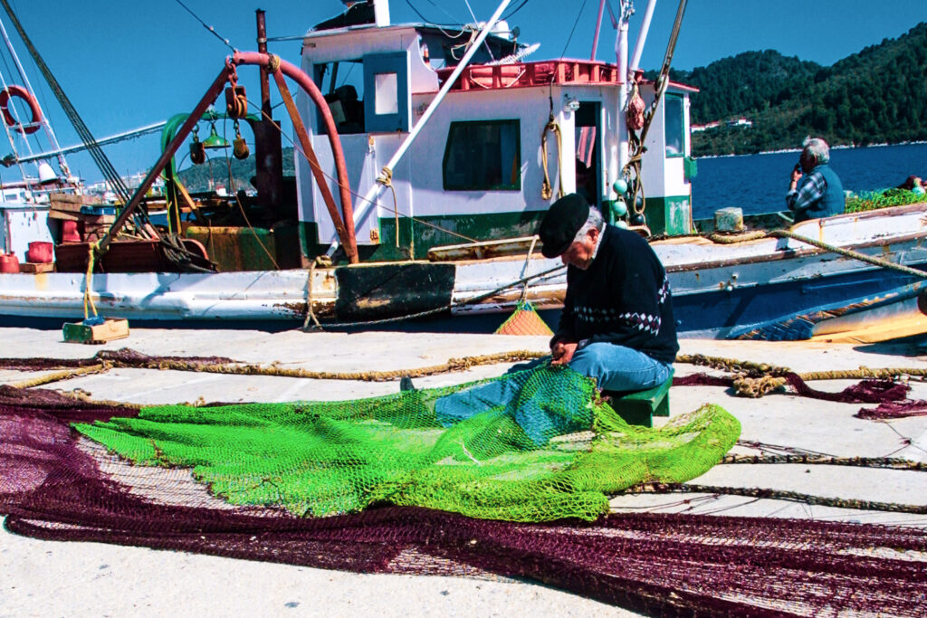 The never-ending task of repairing the nets goes on on the pier at Skiathos